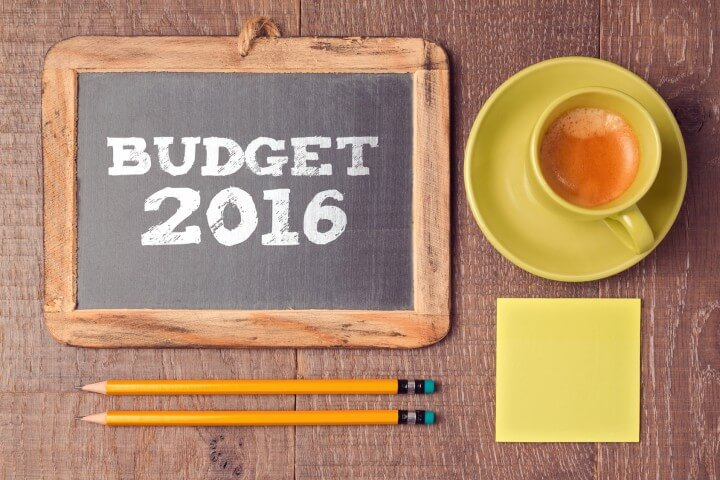 Business concept of budget for 2016 new year. Chalkboard with coffee cup on wooden desk.