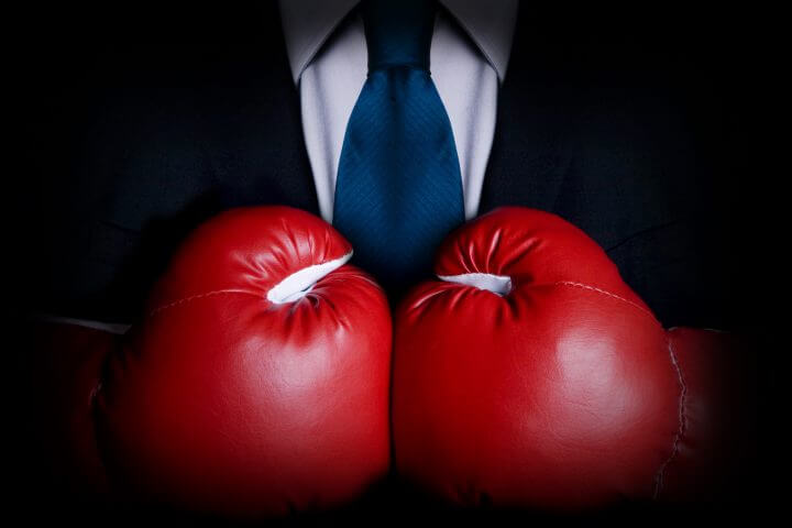 Stock image of person wearing business suit and boxing gloves