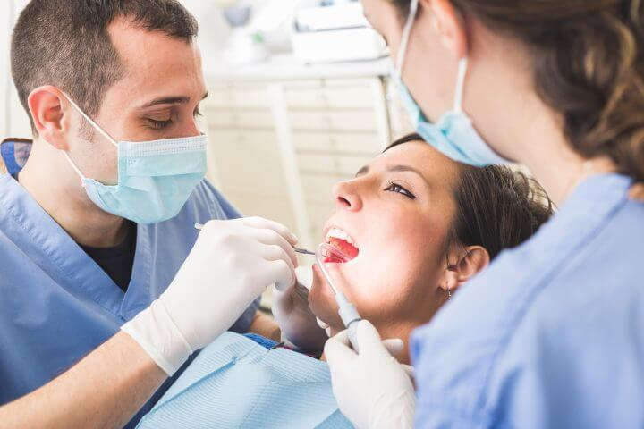 Dentist and Dental Assistant examining Patient teeth. Dentist is a Man, Assistant and Patient are Women. Patient is Smiling and not scared of Dentist.