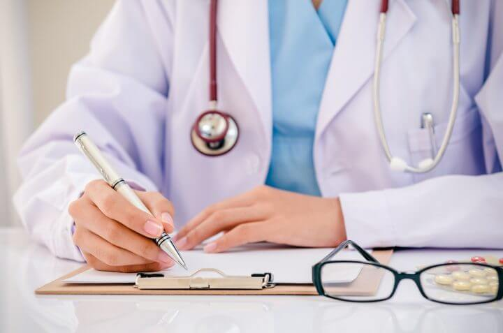 doctor writing record on folder while holding medicine in office
