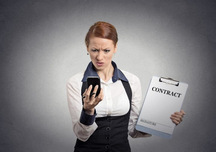 Portrait unhappy skeptical businesswoman holding contract document looking reading news on smart mobile phone isolated office grey wall background. Human face expression emotion of corporate executive