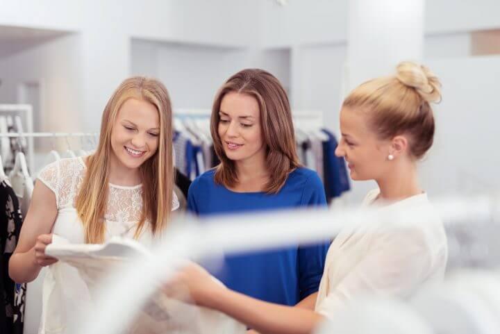 verkäuferin berät kundinnen in einer boutique