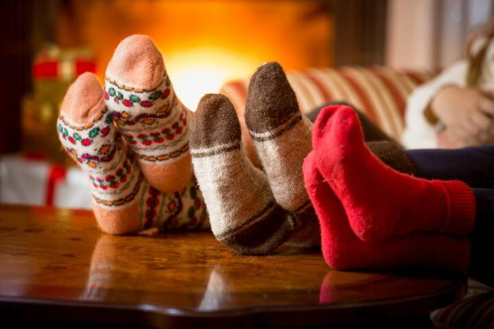 a_family_puts_up_their_feet_by_the_fireplace_with_christmas_presents_in_the_background_at_one_of_our_mountain_cabin_rentals_in_gatlinburg_tn