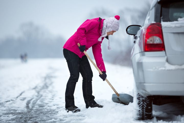 woman with a shovel removing snow around her car