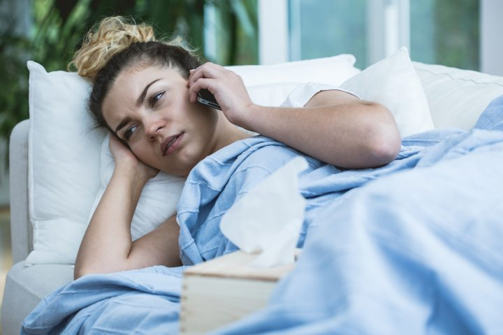 Sick woman with phone and tissues in bed