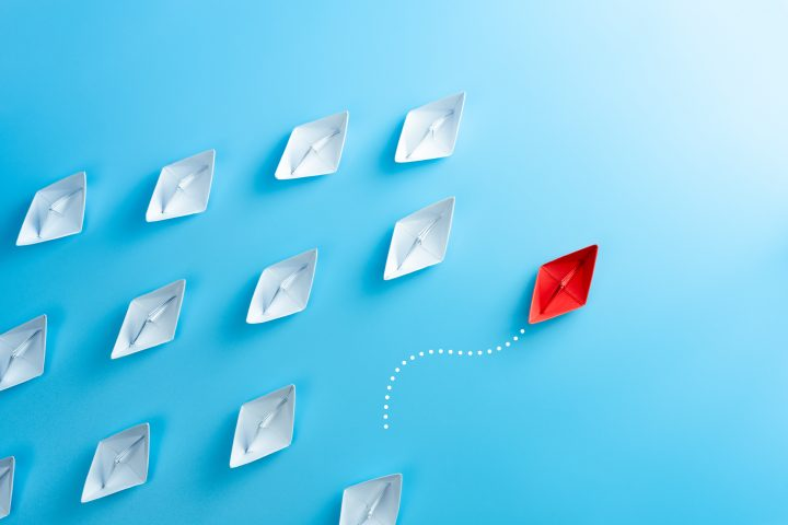 Red paper ship pointing in different way among white paper ship on blue background